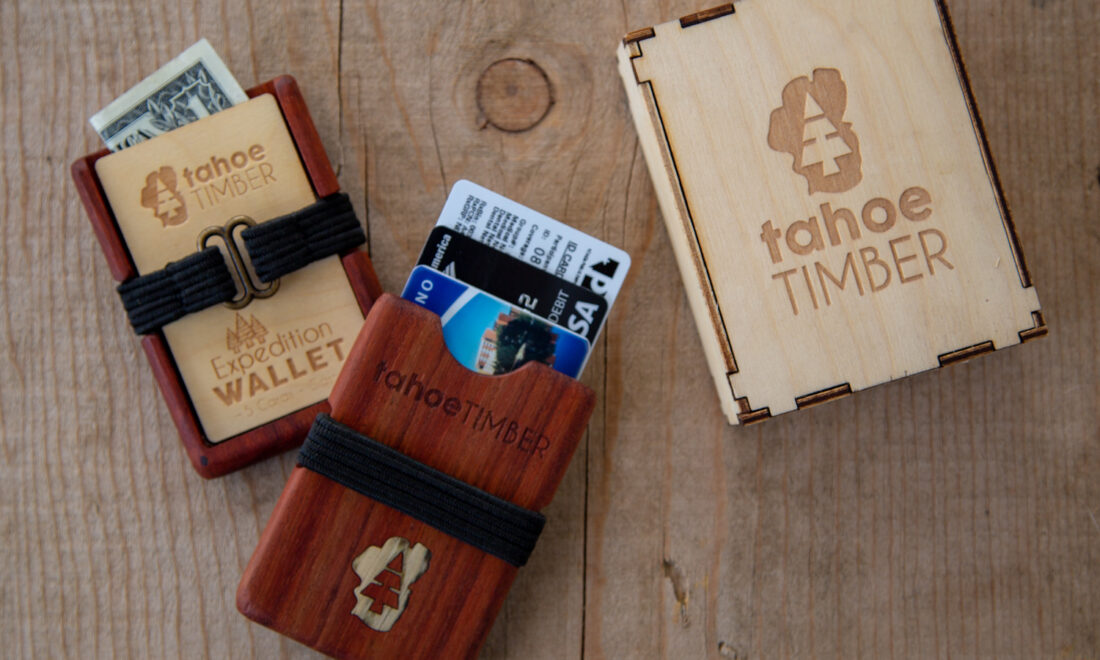 A Tahoe Timber wooden wallet is on display on a piece of wood. Money and various cards can be seen coming from the wallet.