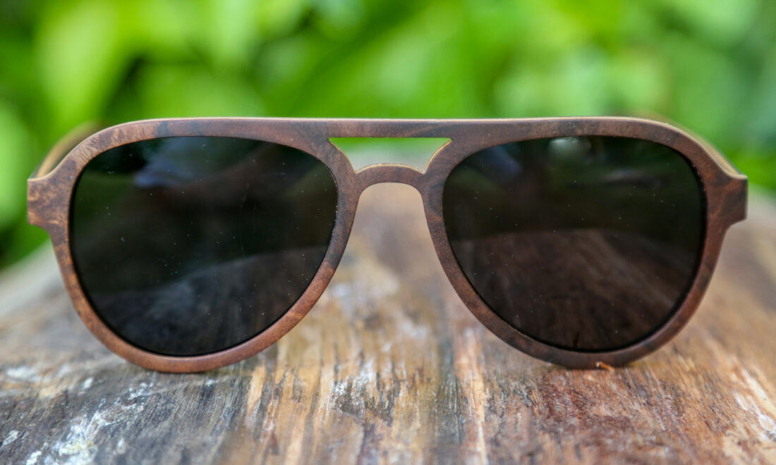Image of wooden sunglasses upon a piece of wood. In the background, green foliage can be spotted.